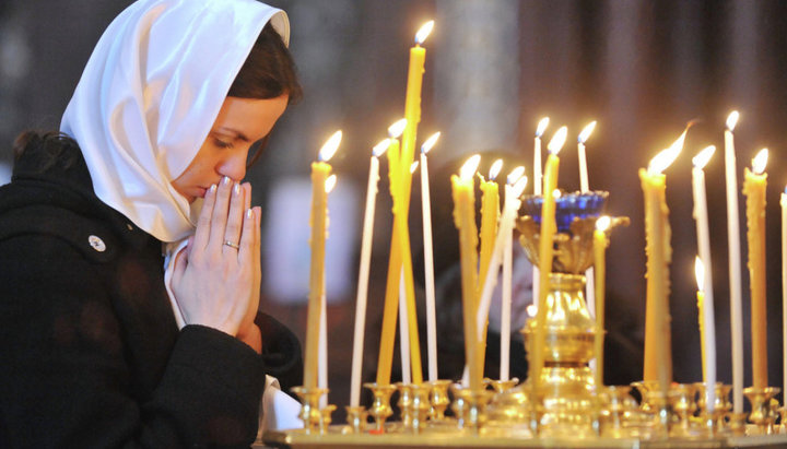 Девушка молится во время богослужения